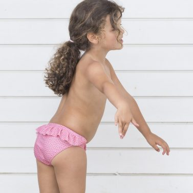 Petit Crabe girl in pink flower Zoe bikini bottoms with ruffles in the back. UV sun protective swimwear for kids.