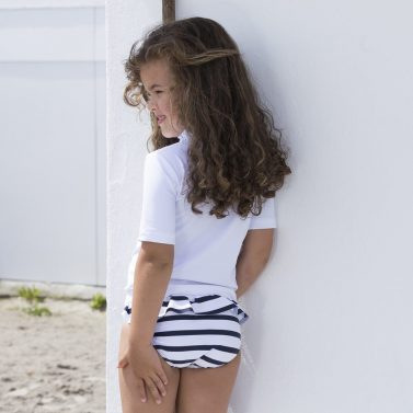 Petit Crabe girl in striped Zoe bikini bottoms with ruffles and Max UV rash guard. Sun protective swimwear for kids.