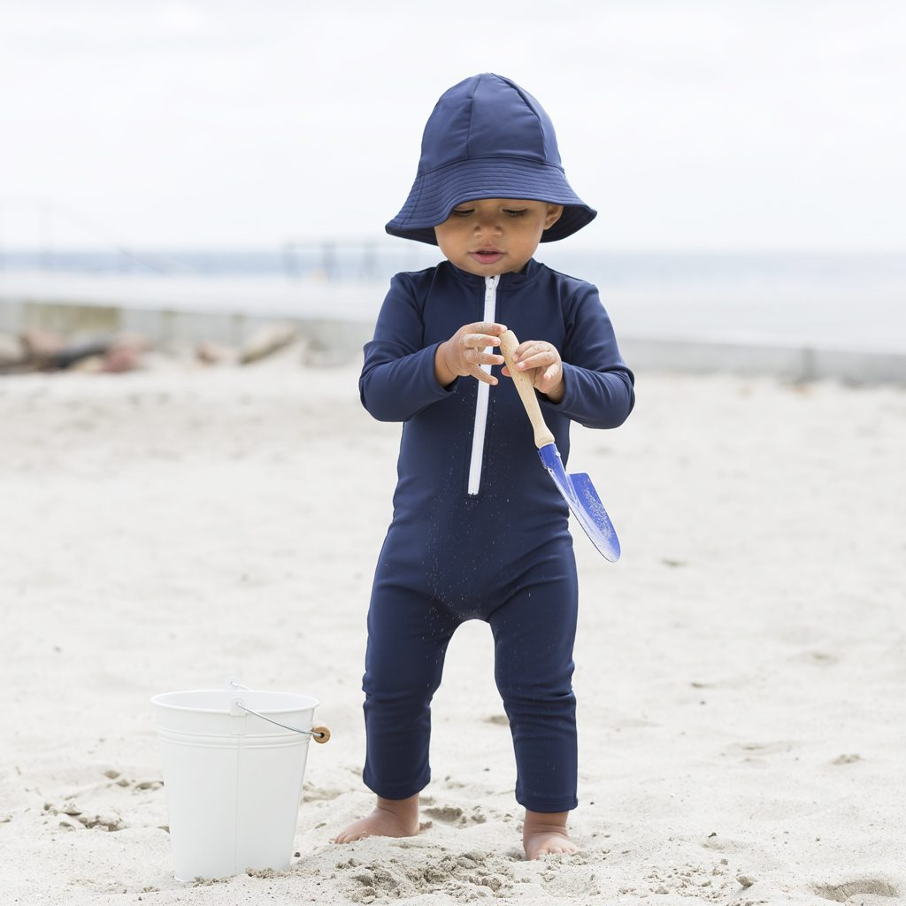 Petit Crabe baby boy in blue Lou CHIEF sunsuit with zipper and Frey sun hat. UV sun protective swimwear for kids.