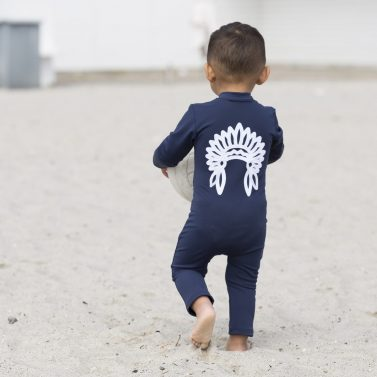 Petit Crabe baby boy in blue Lou sunsuit with chief application on the back. UV sun protective swimwear for kids.
