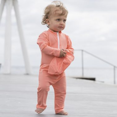 Petit Crabe baby girl in coral Lou STAR sunsuit with zipper and long sleeves. UV sun protective swimwear for