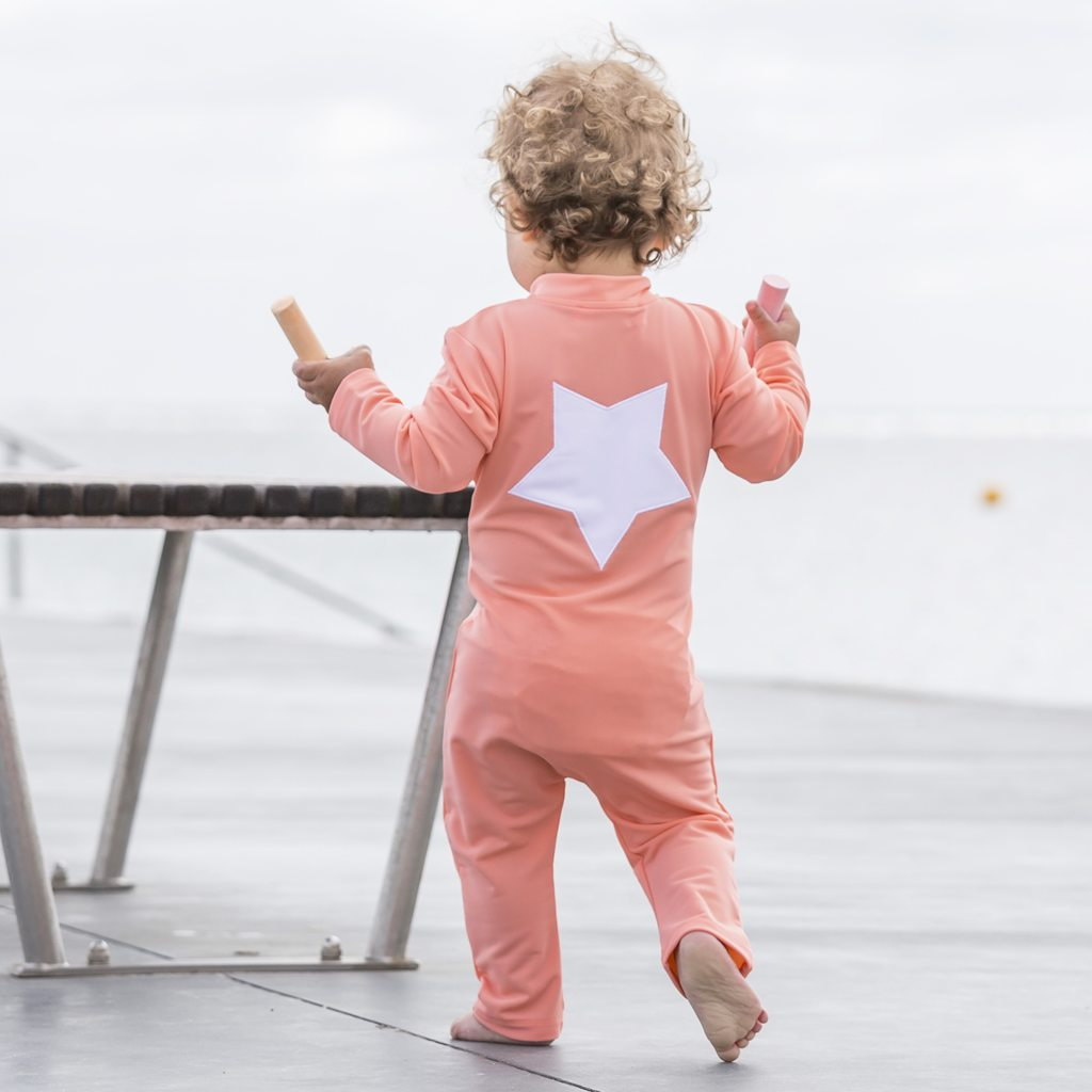 Petit Crabe baby girl in coral Lou sunsuit with star application on the back. UV sun protective swimwear for kids.