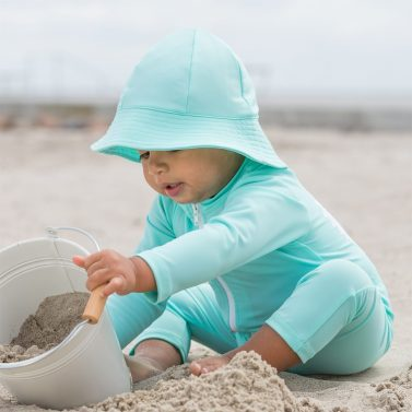 Petit Crabe baby boy in mint Lou CHIEF sunsuit with zipper and Frey sun hat. UV sun protective swimwear for kids.