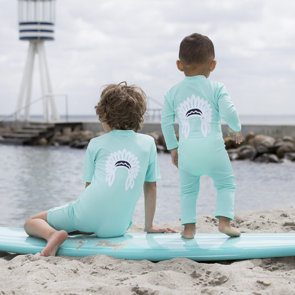 Petit Crabe two boys in mint Lou sunsuits with chief application on the back. UV sun protective swimwear for kids.