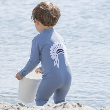 Petit Crabe boy in petrol blue Lou sunsuit with chief application on the back. UV sun protective clothing for kids.
