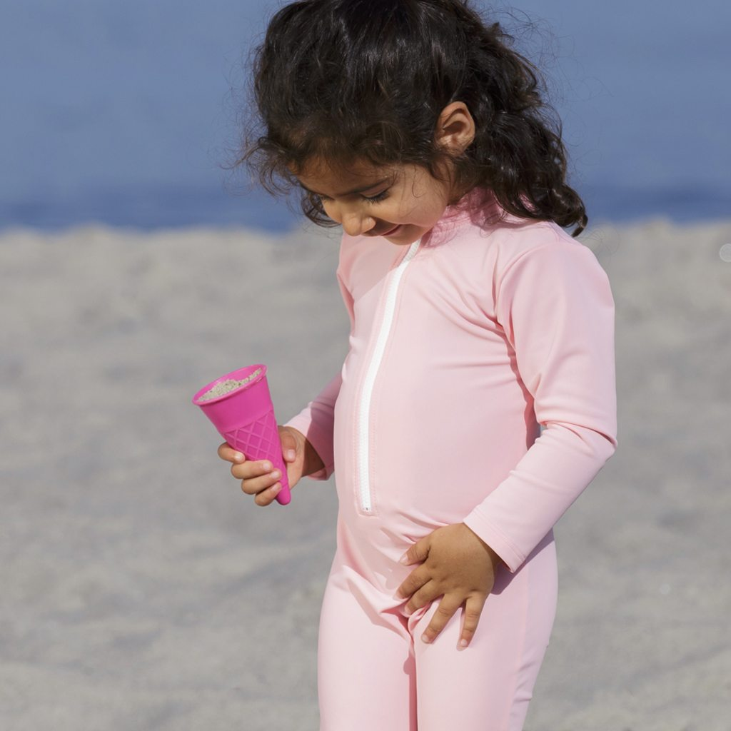 Petit Crabe girl in soft rose Lou ICE CREAM sunsuit with zipper. UV sun protective swimwear for kids.