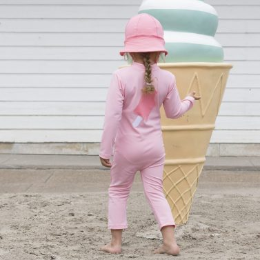 Petit Crabe girl in soft rose Lou ICE CREAM sunsuit and Frey sun hat. UV sun protective swimwear for kids.