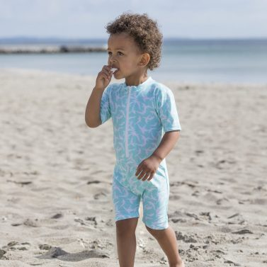Petit Crabe boy in mint dolphin Natsu sunsuit with half zipper. UV sun protective swimwear for children.