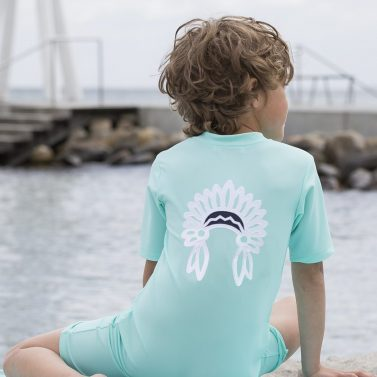 Petit Crabe boy in mint Noe sunsuit with chief application. UV sun-protective clothing for kids.