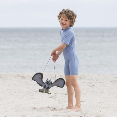 Petit Crabe boy in petrol blue Noe Chief sunsuit with zipper. UV protective swimwear for kids.