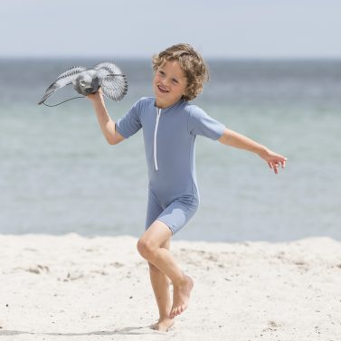 Petit Crabe petrol blue Noe Star sunsuit for kids, boy in sun protective clothing playing