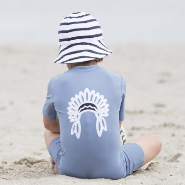 Petit Crabe boy in petrol blue Noe Chief sunsuit and striped Frey sun hat. UV protective swimwear for kids.