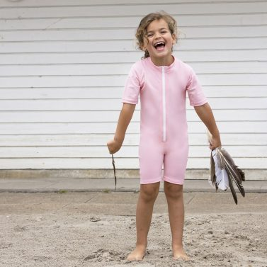 Petit Crabe girl in soft rose Noe Ice Cream sunsuit with zipper. UV sun protective clothing for kids.