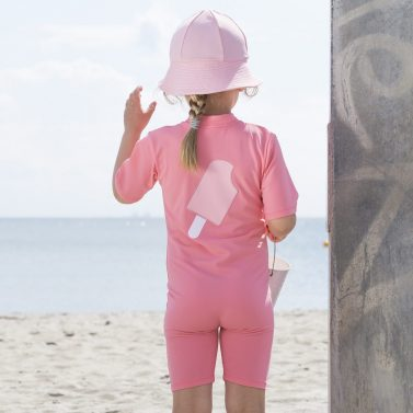 Petit Crabe girl in Noe sunsuit with ice cream application on the back. UV sun protective swimwear for kids.