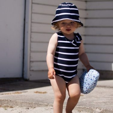 Petit Crabe girl in blue and white striped Elise Swimsuit with cute bow and Frey sunhat