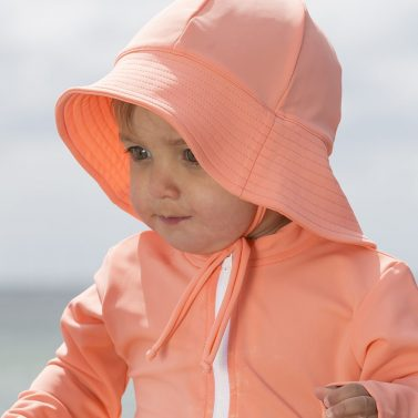 Petit Crabe baby girl in coral Frey sun hat and Etoile rash guard. UV sun protective swimwear for kids.