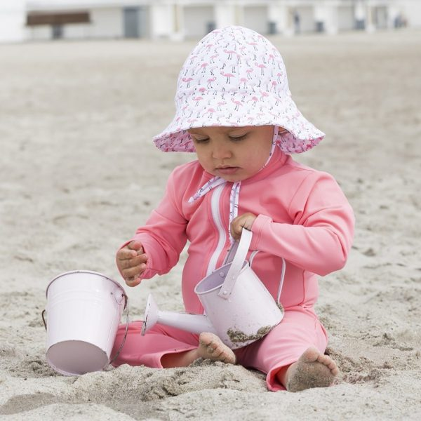 Petit Crabe Baby girl in Flamingo Frey sun hat and sunsuit. UV sun protective swimwear for children.