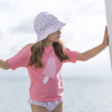 Petit Crabe Baby girl in Flamingo Frey sun hat, rash guard and Zoe bikini bottoms. UV sun protective swimwear for kids.