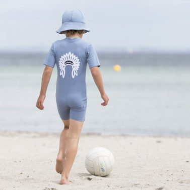 Petit Crabe boy in petrol blue Frey sun hat and Noe CHIEF sunsuit. UV sun-protective swimwear for kids.
