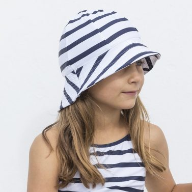 Petit Crabe girl in white/blue striped Frey sun hat and swimsuit. UV sun-protective swimwear for kids.
