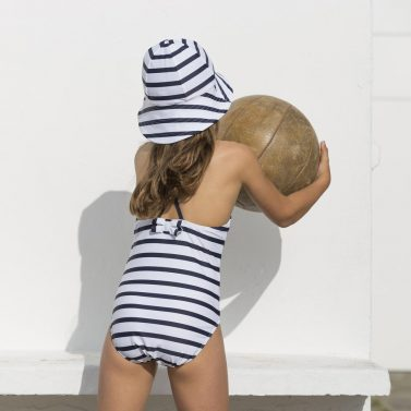 Petit Crabe girl in striped Barbara swimsuit with cute bow on the back and sun hat. UV sun protective swimwear.