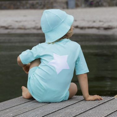 Petit Crabe boy in sky blue Hugo rash guard with star application on the back, and UV sun hat.