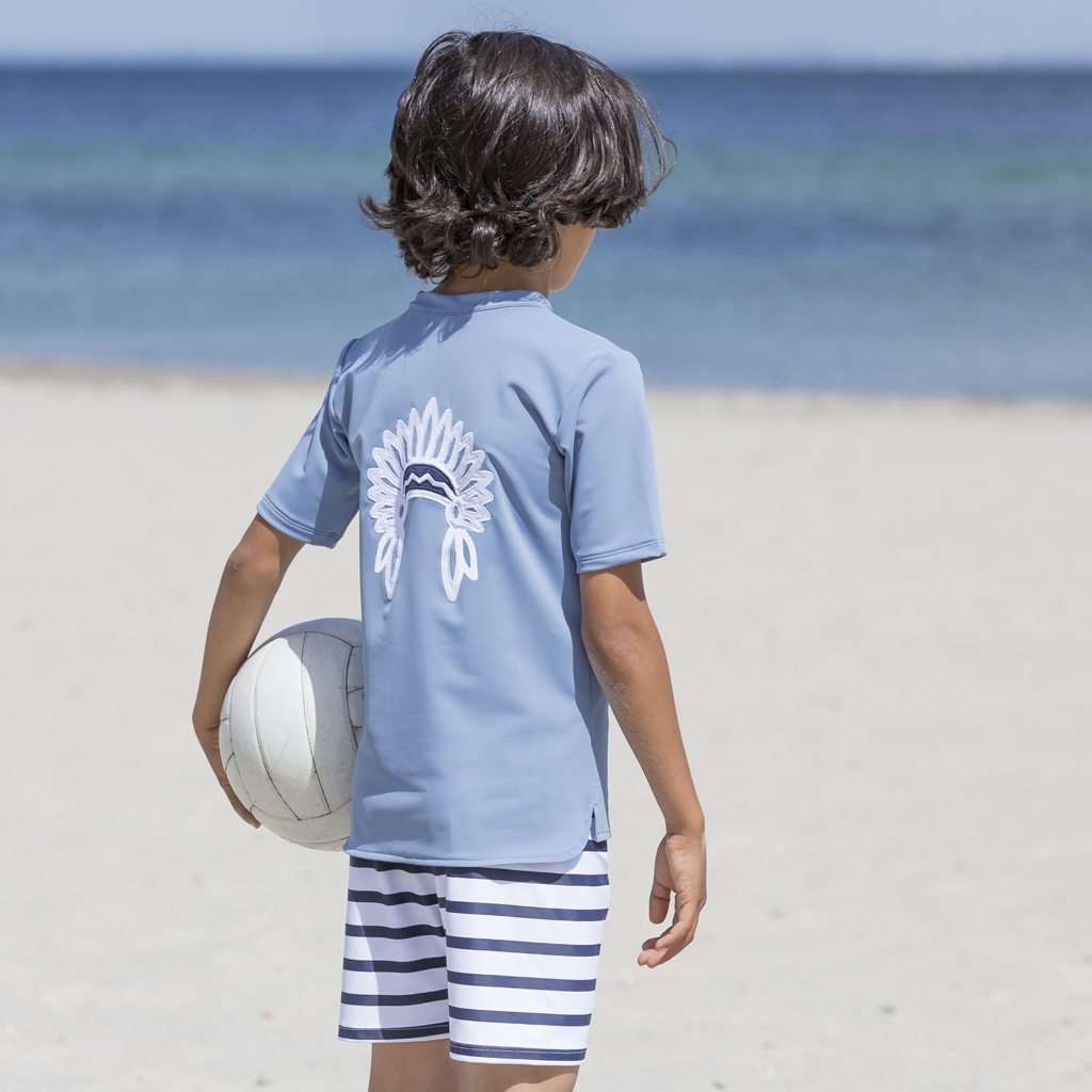 Petit Crabe boy in petrol blue Hugo rash guard with chief application on the back. UV sun protective swimwear for kids.