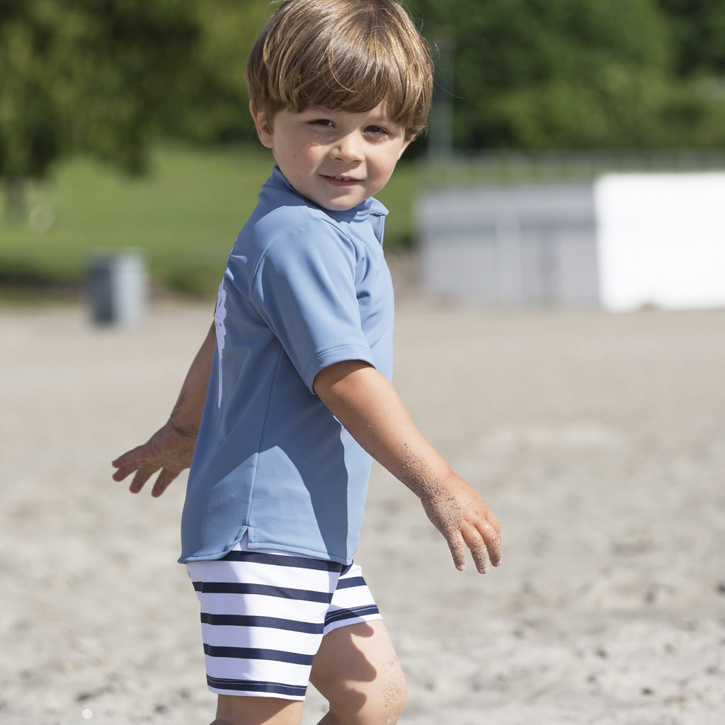 Petit Crabe Boy In Petrol Blue Hugo Chief Rash Guard And Alex Striped Swim Trunks. UV Sun Protective Swimwear For Kids.