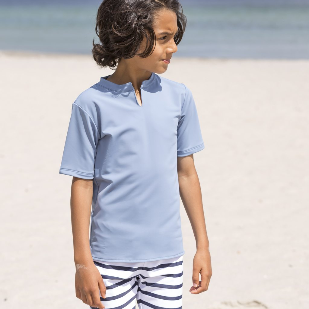Petit Crabe boy in petrol blue Hugo Chief rash guard with short sleeves. UV sun protective swimwear for kids.