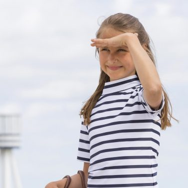Petit Crabe girl in white and blue striped Ash turtleneck swim shirt. UV sun-protective swimwear for kids.