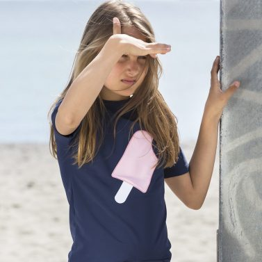 Petit Crabe girl in UV sun protective blue Luna boatneck swim shirt with ice cream application on the front.