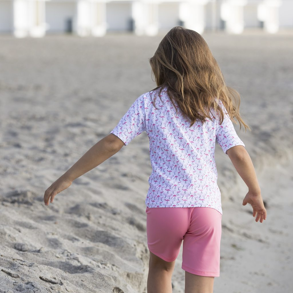 Petit Crabe girl in flamingo Luna boatneck rash guard and Alex badeshorts. UV sun protective swimwear for kids.