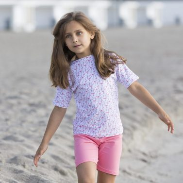 Petit Crabe girl in flamingo UV protective Luna boatneck swim shirt, with short sleeves, and Alex badeshorts.