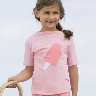 Petit Crabe girl in UV sun protective soft rose Luna boatneck swim shirt with ice cream application on the front.