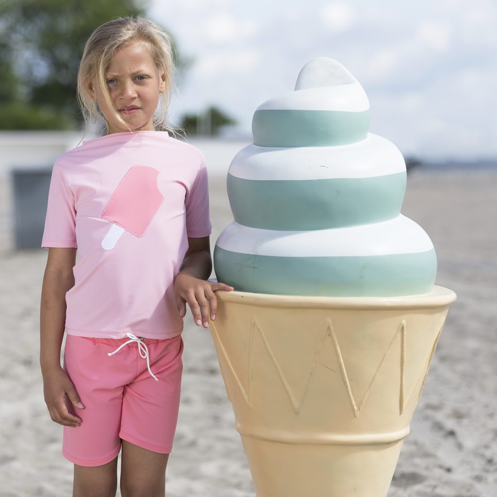 Petit Crabe soft rose Luna rash guard, with ice cream application, and Alex swim shorts. UV sun protective swimwear for kids.