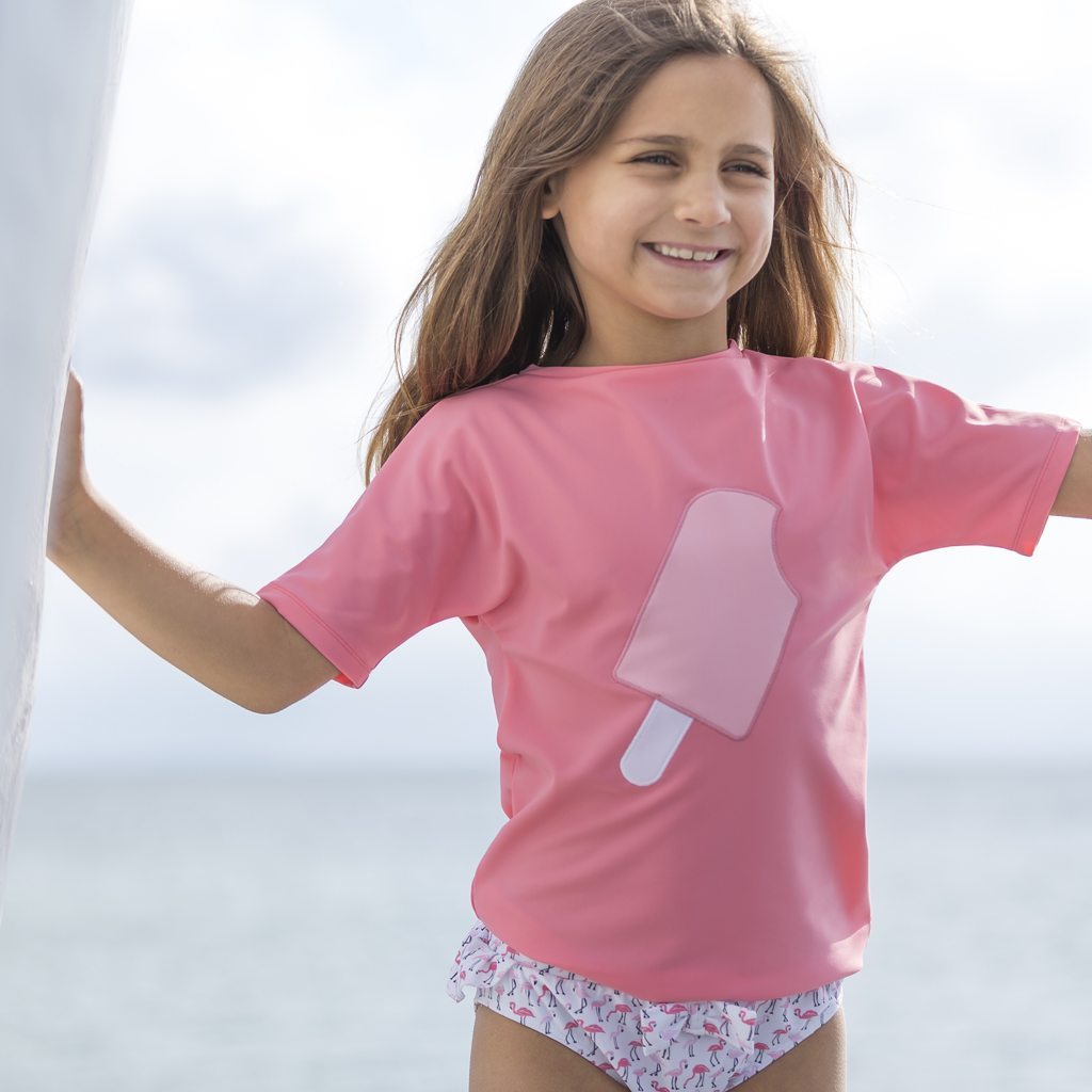 Petit Crabe girl in UV sun protective watermelon-pink Luna boatneck swim shirt with ice cream application on the front.