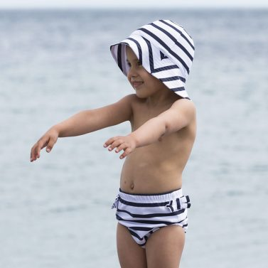 Petit Crabe girl in white and blue striped swim nappy and sun hat. UV sun protective swimwear for kids.