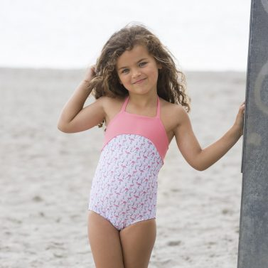 Petit Crabe girl in Flamingo Ines Swimsuit, sun protective swimwear for children.