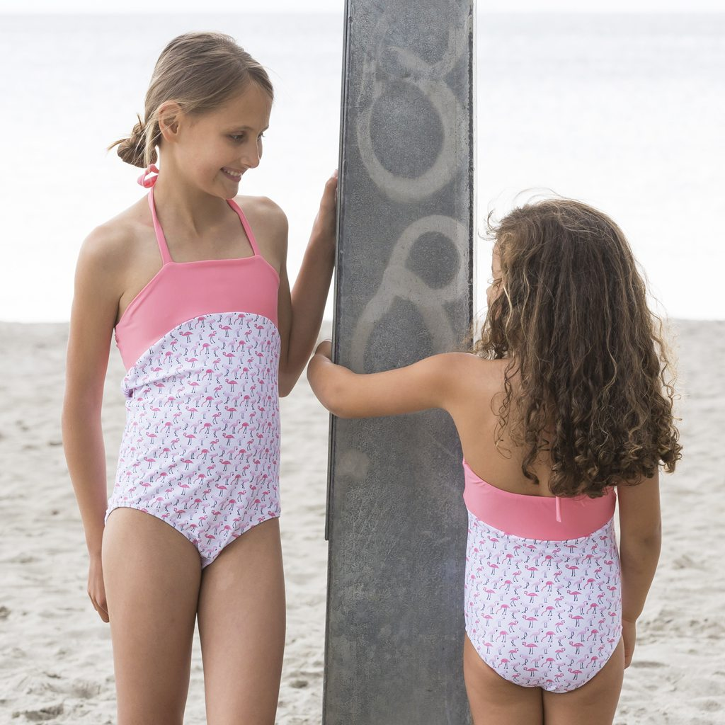 Petit Crabe two girls in Flamingo Ines Swimsuits, sun protective swimwear for kids.