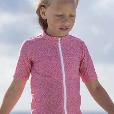 Petit Crabe girl in pink flower Fran rash guard with zipper. UV sun protective swimwear for children.