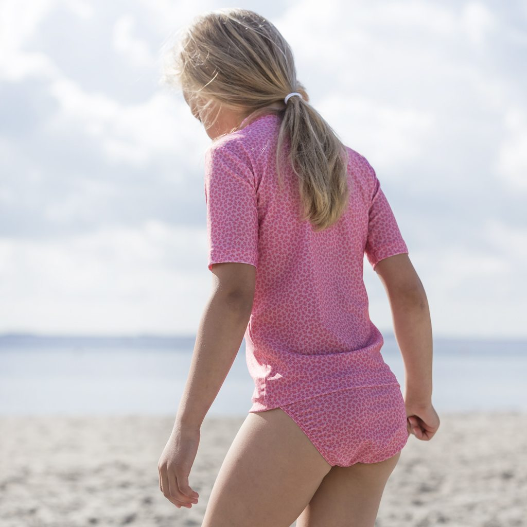 Petit Crabe girl in pink flower Fran zipper rash guard and Louise bikini. UV sun protective swimwear for kids.