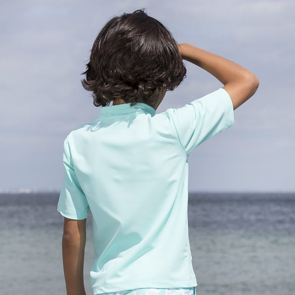 Petit Crabe boy in mint Max rash guard with short sleeves. UV sun protective swimwear for children.