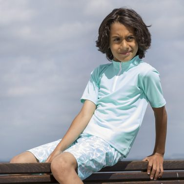 Petit Crabe boy in UV protective mint Max rash guard with half zipper, and board shorts with dolphin print.