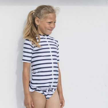 Petit Crabe girl in white and blue striped Fran zipper rash guard and Zoe bikini bottoms. UV sun protective swimwear.