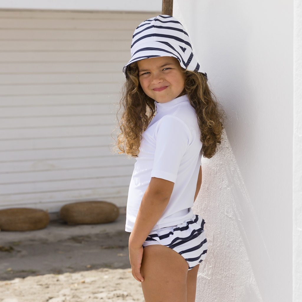 Petit Crabe girl in white Max rash guard, white and blue striped Frey sun hat and Zoe bikini bottoms with ruffles.