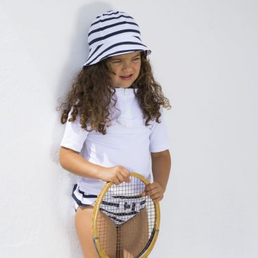 Petit Crabe girl in UV protective white Max rash guard with half zipper, and white and blue striped Frey sun hat.