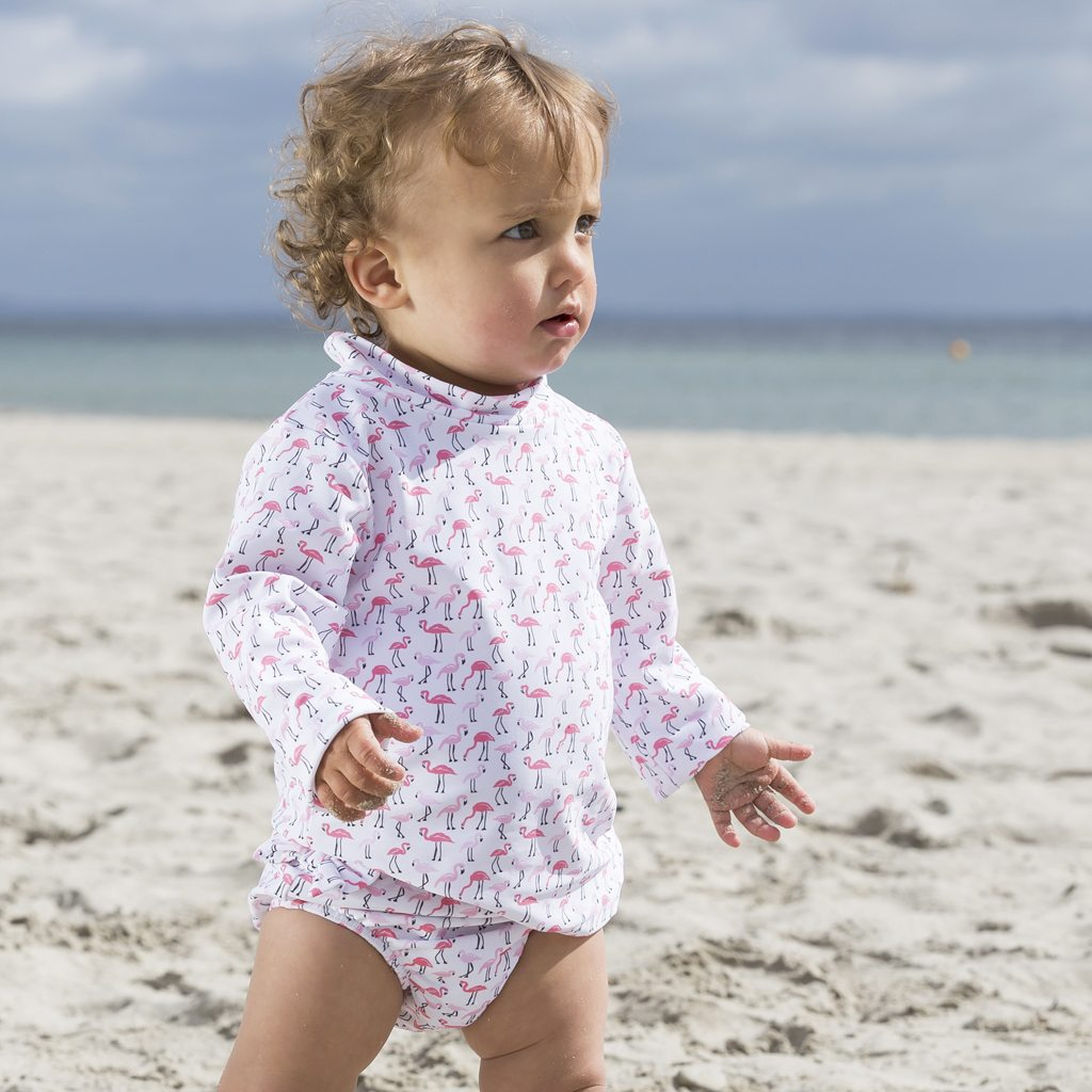 Petit Crabe baby girl in flamingo Casey rash guard and Lea swim nappies. UV sun protective swimwear for kids.