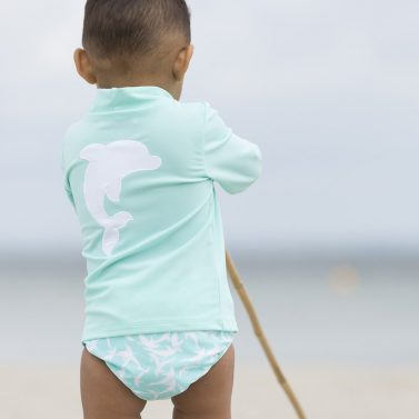 Petit Crabe baby boy in mint Casey turtleneck rash guard with dolphin application on the back. UV swimwear for kids.