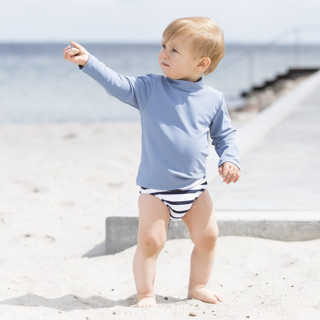 Petit Crabe boy in Casey Chief turtleneck rash guard and striped swim nappy. UV sun protective swimwear kids.