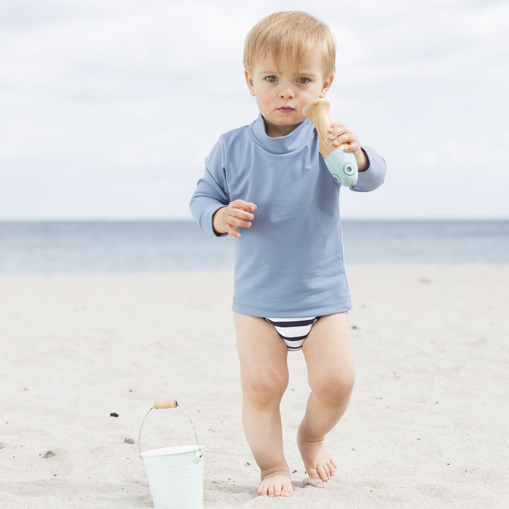 Petit Crabe boy in petrol blue Casey Chief turtleneck swim shirt. UV sun protective swimwear for kids.